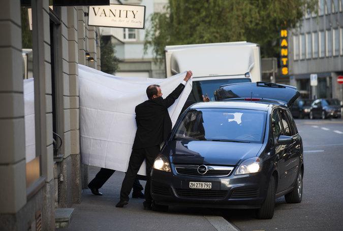 Заарештованих керівників ФІФА виводять з готелю в Цюриху, прикриваючи простирадлами. Фото The New York Times